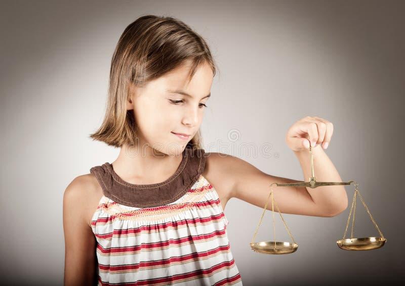 Échelle de justice de fixation de fille photo stock