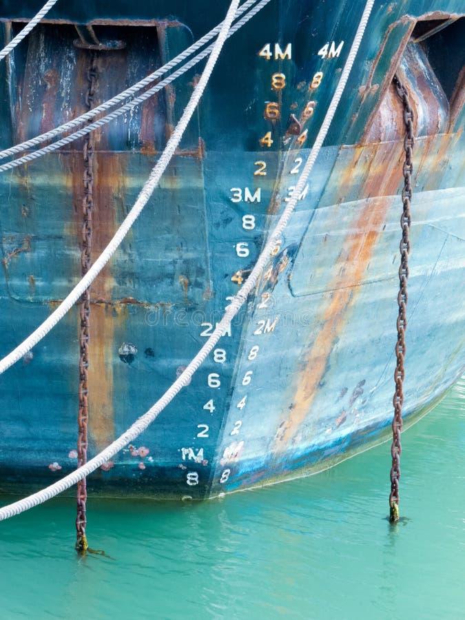 Échelle de profondeur sur la proue du bateau ancré dans le bleu sale photos libres de droits