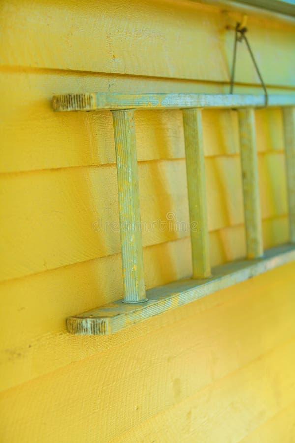 Échelle en bois accrochant sur le mur jaune de maison photo libre de droits
