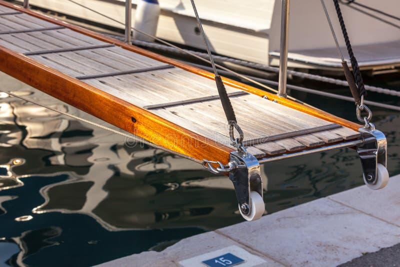 Échelle en bois sur le yacht marin restant dans le port photographie stock