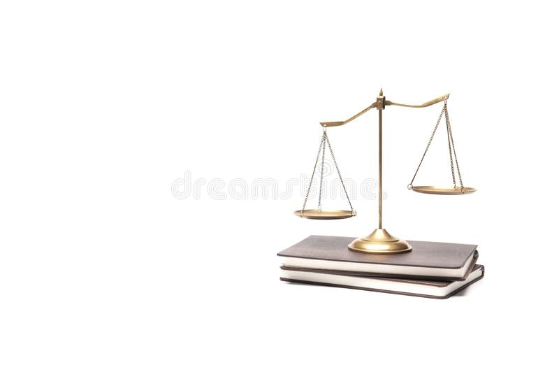 Échelle en laiton d'équilibre d'or placée sur les livres de cru d'isolement sur le fond blanc image libre de droits
