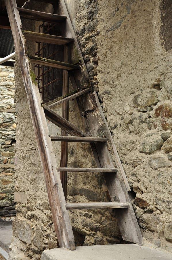 Échelle et mur en pierre en bois cassés vieux par village photographie stock