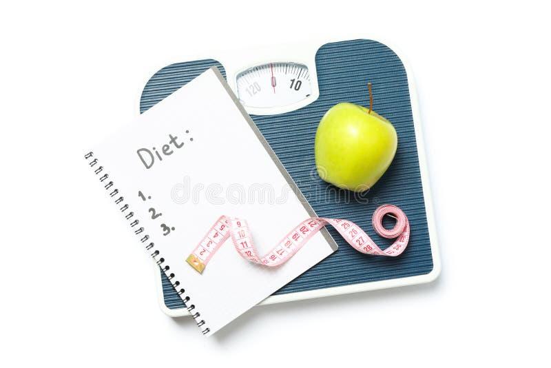 Échelles, bande de mesure, pomme et cahier images libres de droits