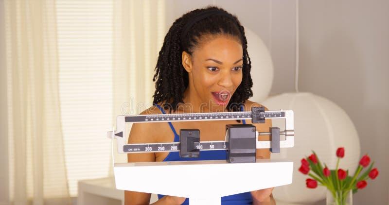 Échelles de lecture heureuses de femme de couleur mignonne photo libre de droits