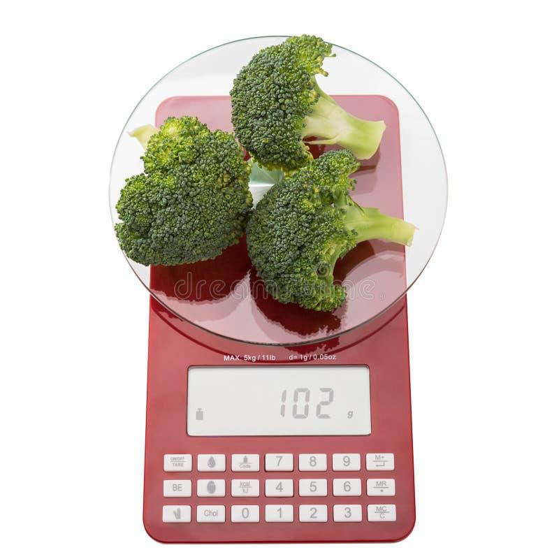 Échelles de nourriture et brocoli frais vert images libres de droits