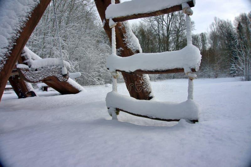 Échelons d'une échelle de corde couverte dans la neige épaisse photos stock