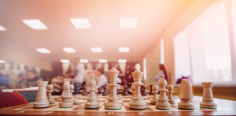 Échiquier avec des figures pour le jeu, lumière de point culminant Les gens jouent à l'arrière-plan image stock