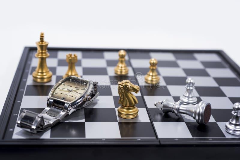 Échiquier d'isolement sur le fond blanc Figures d'or et argentées avec la montre de main photographie stock libre de droits