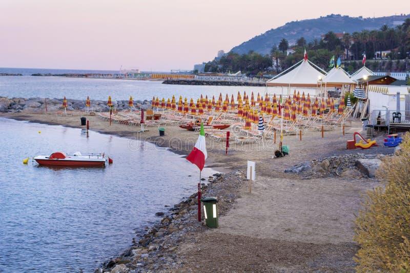 Échouez avec des parapluies au coucher du soleil dans San Remo, Italie photos libres de droits
