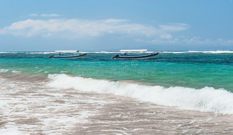 Échouez dans Bali avec des vues de mer avec deux bateaux avec une ligne de ressac un jour ensoleillé avec des nuages sur l'horizo photographie stock libre de droits