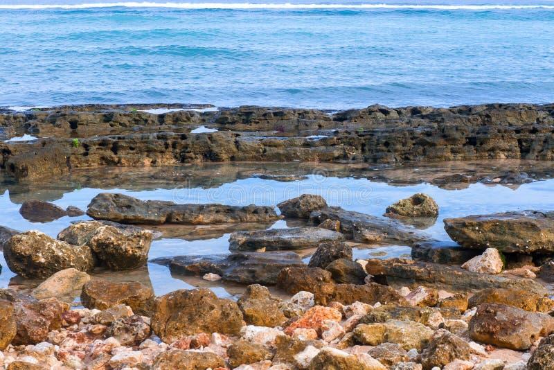 Échouez la ligne de côte avec les pierres et l'océan de cailloux, à sable jaune et azuré photo libre de droits