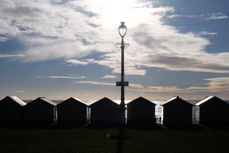Échouez la plage de Brighton de huttes silhoutted par le coucher de soleil images stock