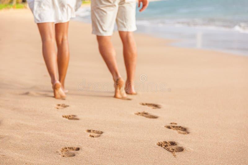 Échouez les couples marchant nu-pieds sur le sable - empreintes de pas photographie stock libre de droits