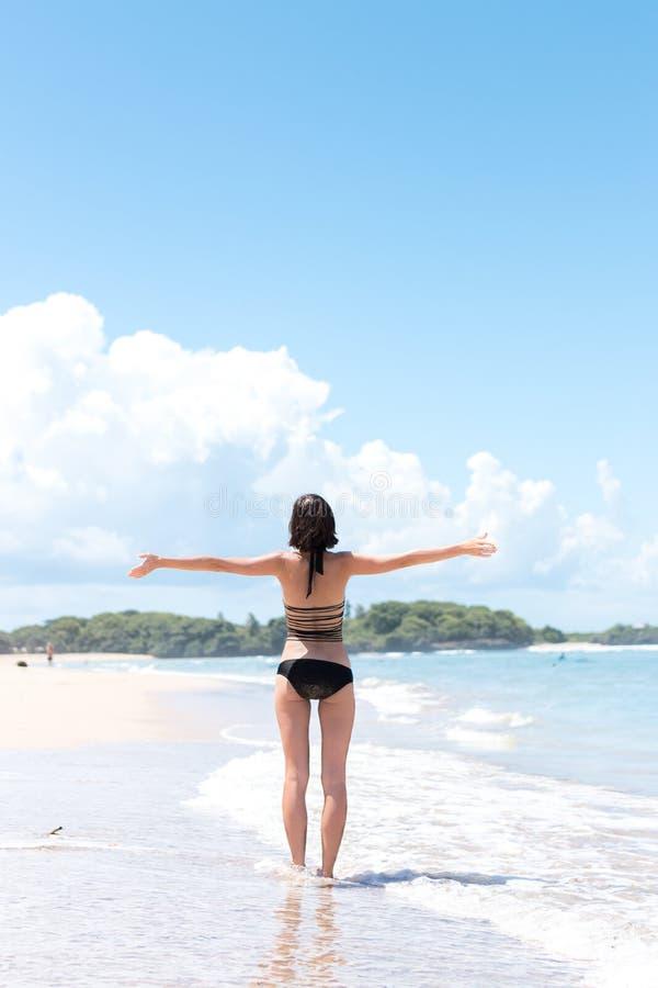 Échouez les vacances Femme heureuse appréciant le jour ensoleillé à la plage Ouvrez les bras, la liberté, le bonheur et le bonheu photos libres de droits