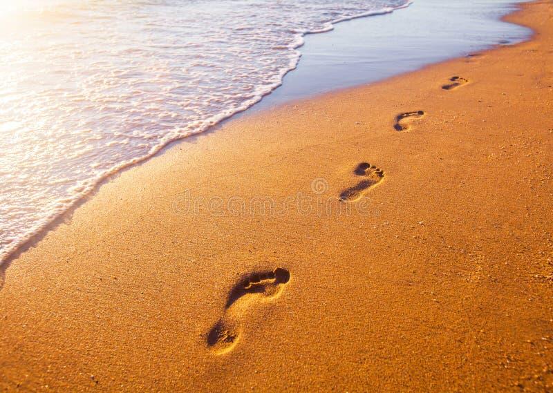 Échouez, vague et empreintes de pas au temps de coucher du soleil image libre de droits