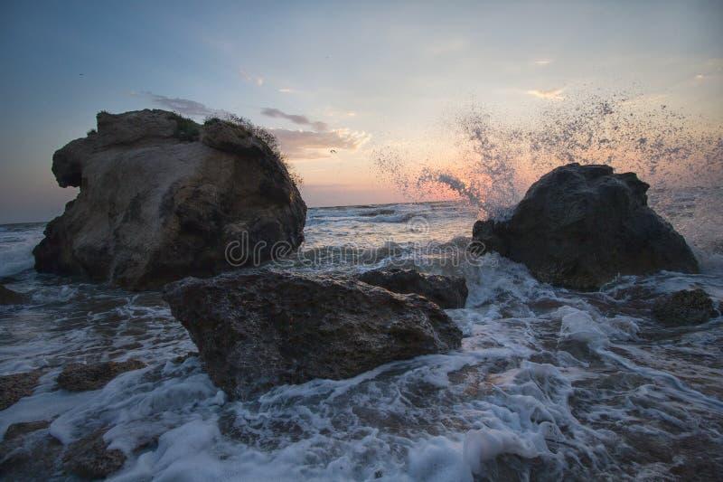 Éclaboussant les vagues ont battu contre les roches sur la plage au coucher du soleil photographie stock libre de droits