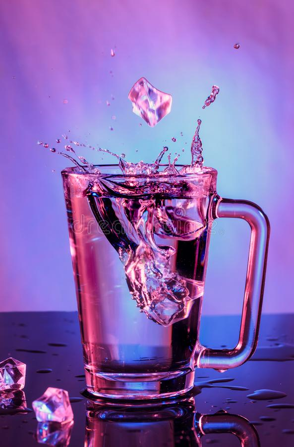 Éclabousse de l'eau Glaçons en baisse dans un verre de l'eau sur a photographie stock libre de droits