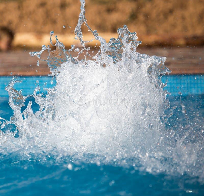 Éclaboussement de l'eau dans la piscine comme fond photos stock