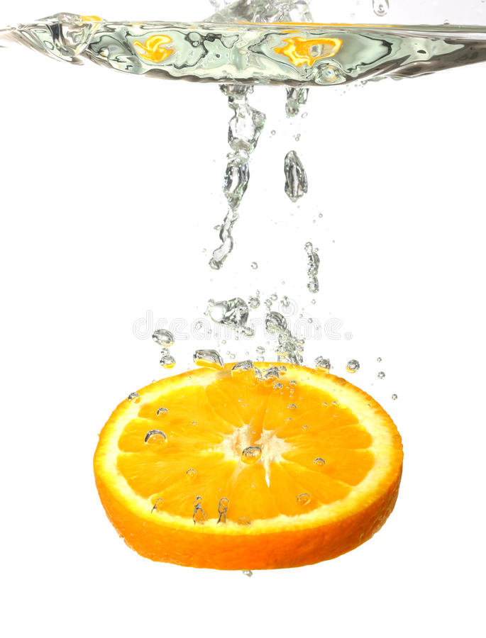 Éclaboussement de l'orange dans l'eau photo stock
