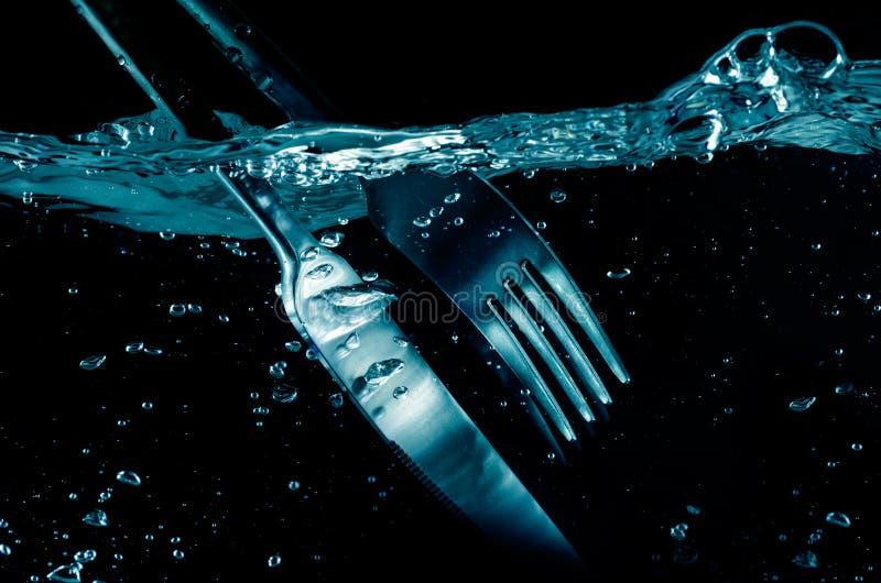 Éclaboussement de la fourchette et du couteau dans l'eau photos libres de droits