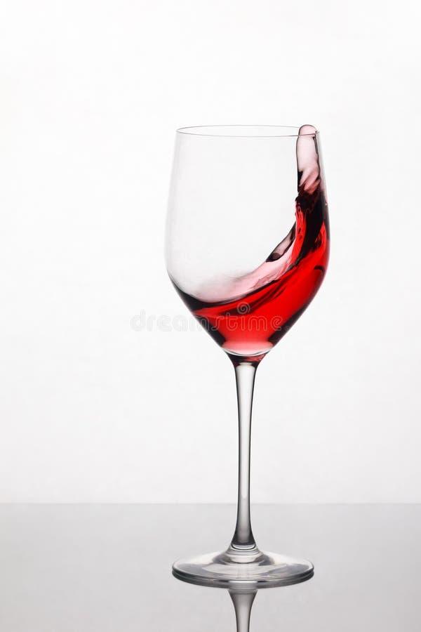 Éclaboussement et vin rouge mobile dans le verre à vin se tenant sur le fond léger avec la réflexion sur le support photos libres de droits