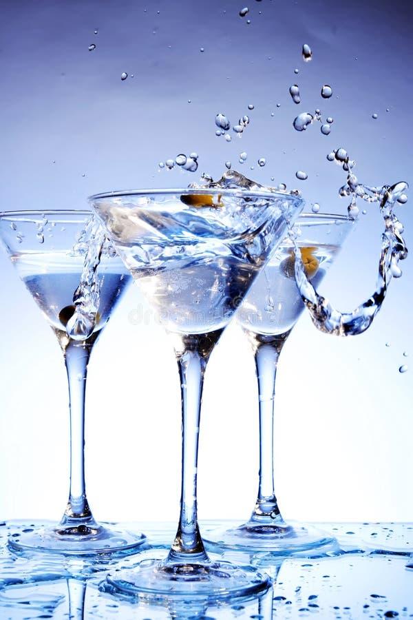 Éclaboussez martini sur le bleu images stock
