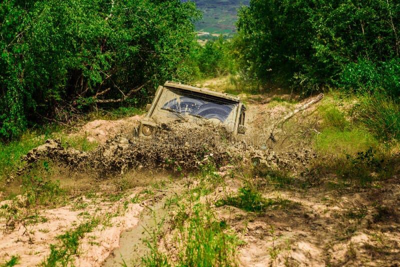 Éclaboussure de boue et d'eau dans l'emballage tous terrains Mudding off-roading par un secteur de boue ou d'argile humide Voies  photographie stock libre de droits