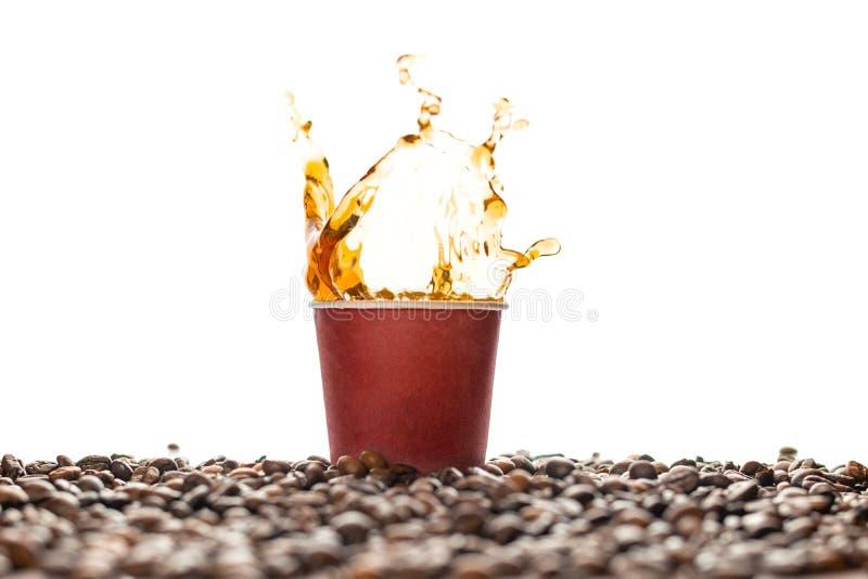 Éclaboussure de café dans la tasse de papier jetable brune avec des grains de café d'isolement sur le blanc images stock