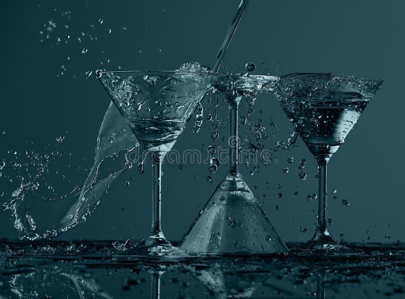Éclaboussure de l'eau en verre de martini images libres de droits