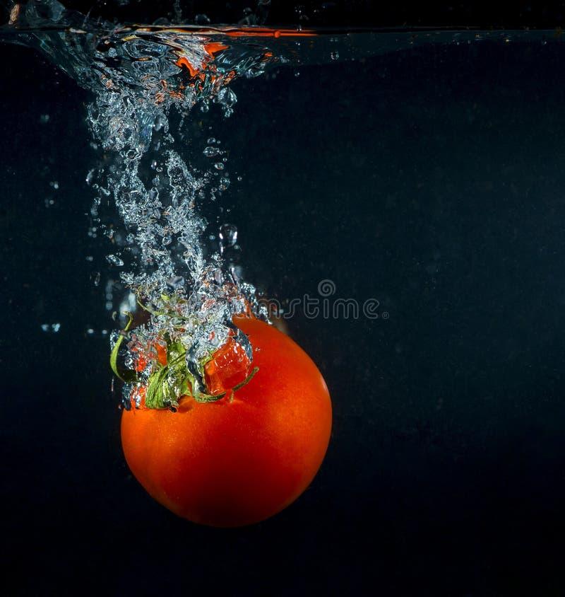 Éclaboussure de tomate de photographie à grande vitesse dans l'eau au-dessus du noir photos stock