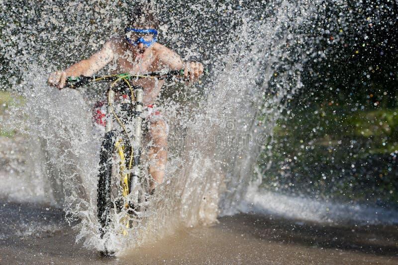 Éclaboussure inclinée de vélo de l'eau de Mountainbiker photographie stock libre de droits