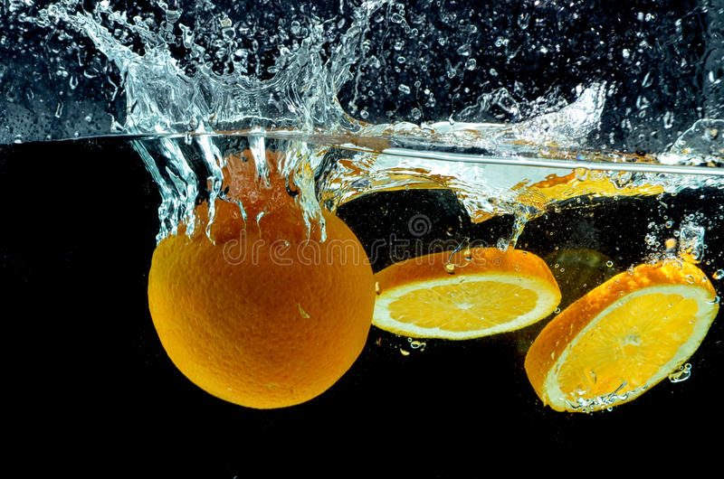 Éclaboussure orange de fruit sur l'eau photos stock