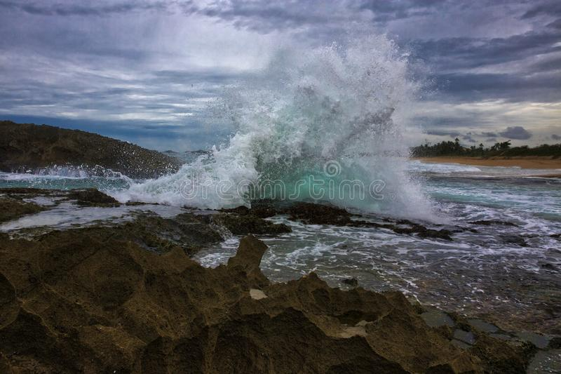 Éclaboussure puissante contre des formations de roche photographie stock