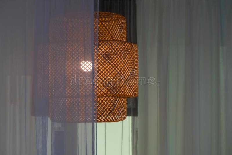 Éclairage de pièce - un lustre fait en bambou, couvert de rideau images libres de droits