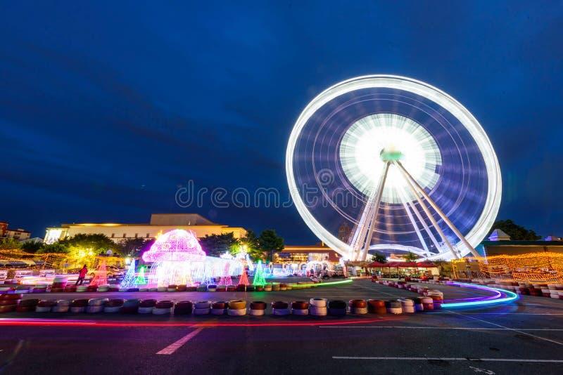 Éclairage léger de voiture de jouet de tache floue avec la roue de ferris pour l'enfant en parc d'attractions images libres de droits