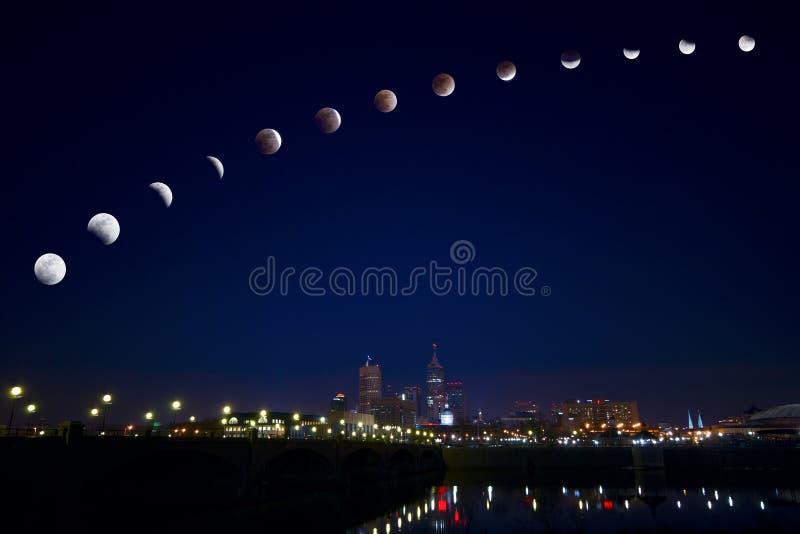 Éclipse de lune au-dessus de ville image stock