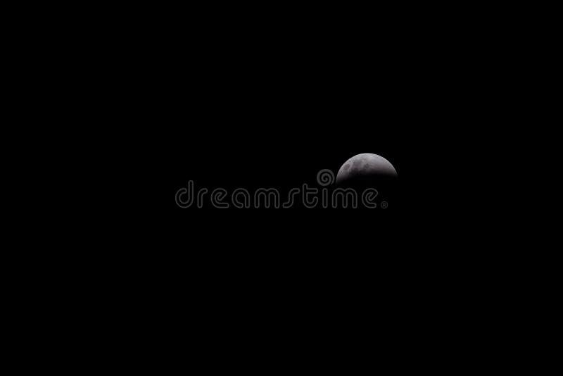 Éclipse de lune sur le fond noir photos stock