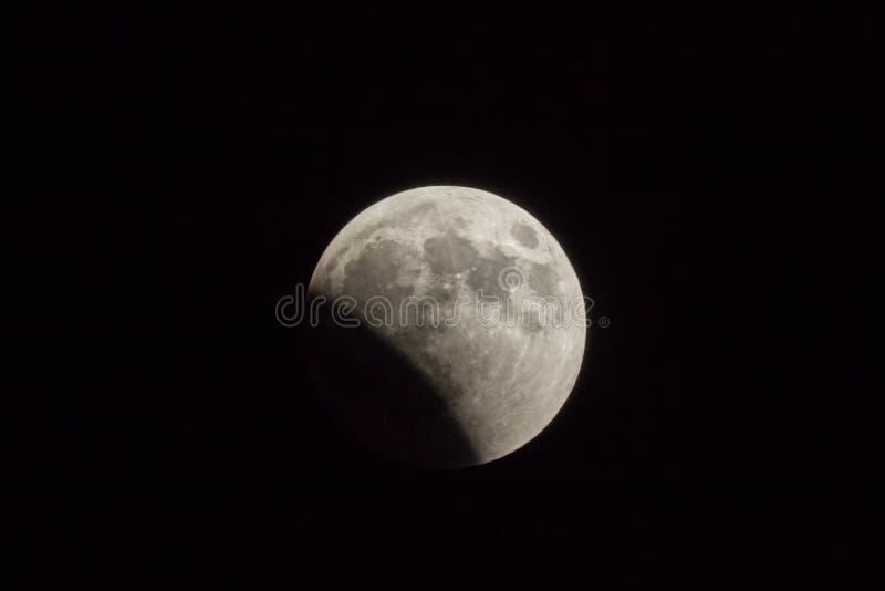 Éclipse lunaire partielle dans la nuit d'été au-dessus du désert de Judean près de la ville de Mitzpe Ramon en Israël images stock