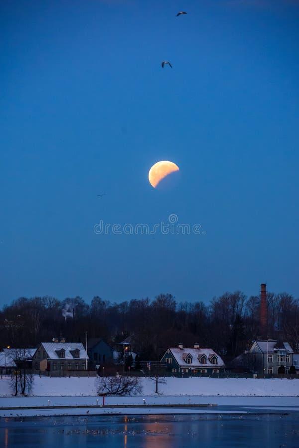Éclipse partielle de lune au-dessus de Kipsala à Riga, Lettonie image stock