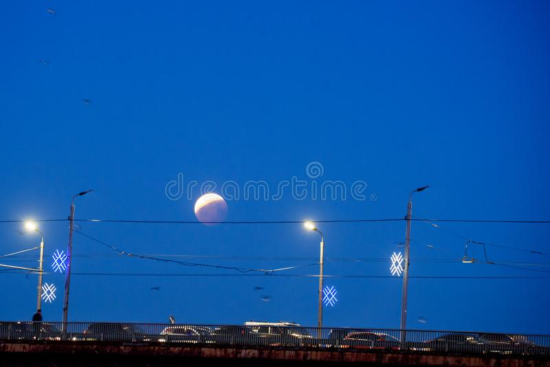 Éclipse partielle de lune au-dessus de pont à Riga images stock