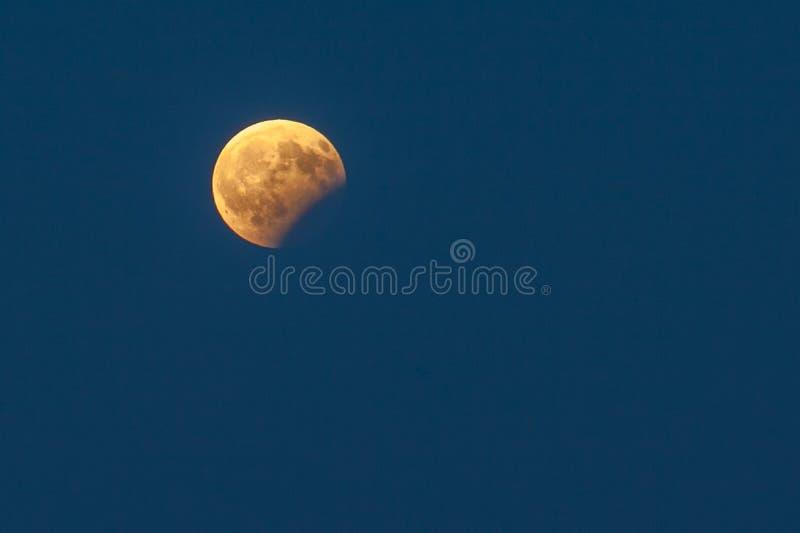 Éclipse partielle de lune dans un ciel bleu image libre de droits