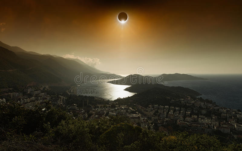 Éclipse solaire totale en ciel rougeoyant rouge foncé au-dessus de ville de bord de la mer photos libres de droits