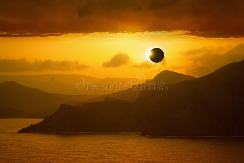 Éclipse solaire totale, silhouettes des montagnes en ciel rougeoyant rouge images stock