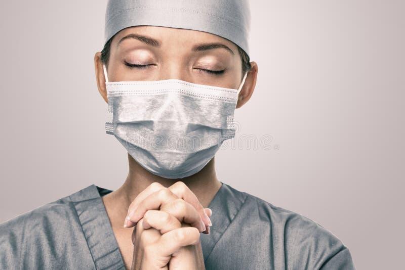 Éclosion de Coronavirus COVID-19 Un médecin priant pour obtenir de l'aide Portrait d'une jeune femme soignante espérant un avenir photos stock