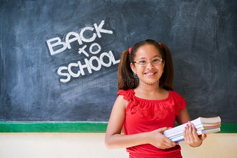 École d'éducation et fille heureuse souriant tenant des livres dans la classe image libre de droits