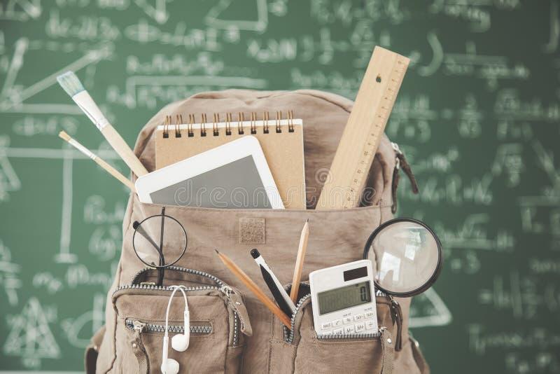 École de sac à dos avec des approvisionnements devant le tableau vert photographie stock