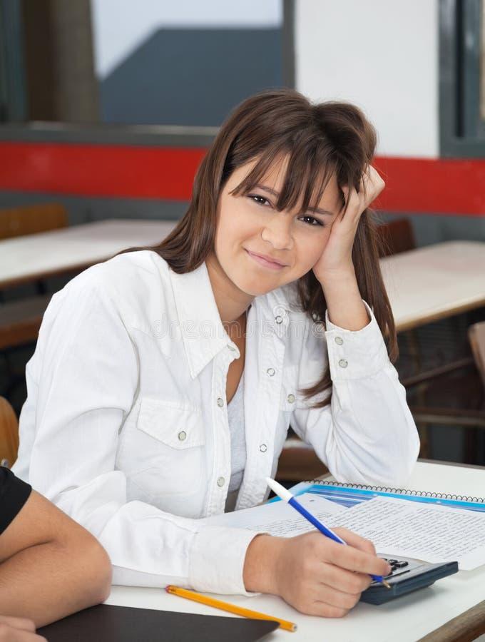 Écolière adolescente à l'aide de la calculatrice au bureau photographie stock