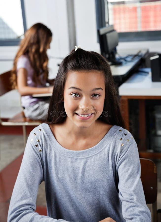Écolière adolescente souriant dans la classe d'ordinateur images libres de droits