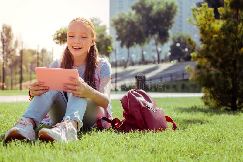Écolière aimable communiquant en ligne avec ses parents photo libre de droits