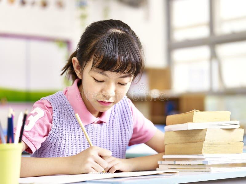 Écolière asiatique étudiant dans la salle de classe photographie stock libre de droits